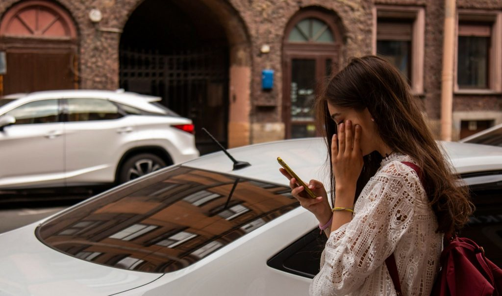 Woman looks at phone on street.