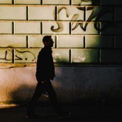 Silhouette of a man walks down a side street.