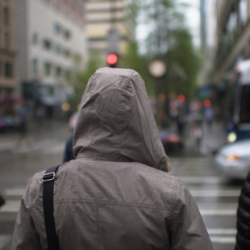 A hooded figure walks through the rain down the street.